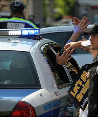 Bruins team players touched the hands of fans as they left in a Boston Police cruiser.