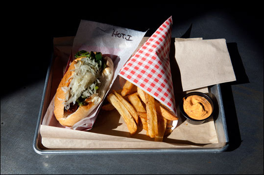 A hot Italian sausage with a side of Belgian fries at Wurstkuche in the downtown arts district.