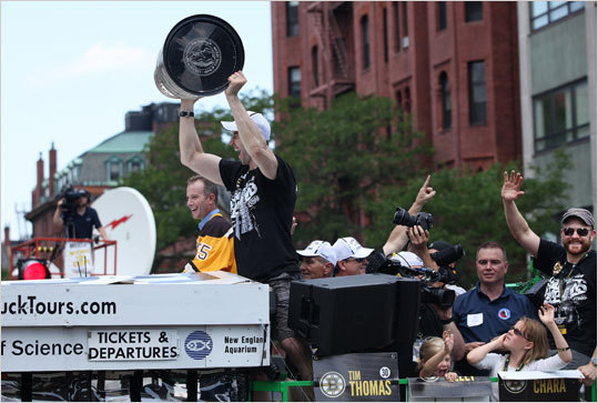 Bruins captain Zdeno Chara held the cup, and MVP Tim Thomas waved while rolling through Copley Square.