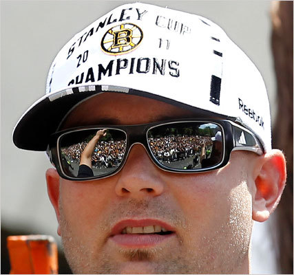 Spectators at the rolling parade are reflected in the sunglasses of Bruins center Marc Savard.