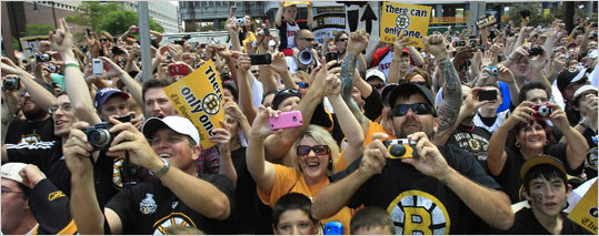 Bruins fans took pictures as the duck boats loaded with Bruins rolled by them.