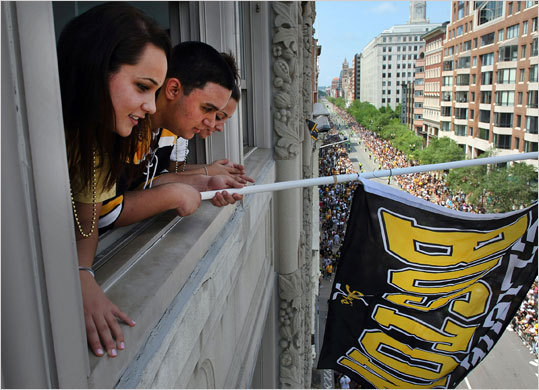 During the Bruins rolling rally, Sara Zavarelli from Stoneham and Nick Todisco from Meford waved a flag from the office window of Karmaloop company on Boylston Street.