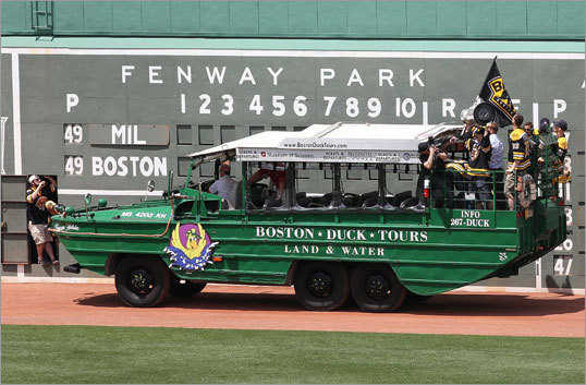 If you look closely you can see Mark Recchi holding the Stanley Cup as a duck boat makes its way in front of the Green Monster.