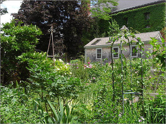 The host group's garden now has a shed with an attached greenhouse, a wrought-iron fence and gravel pathways, and it contains 63 individual plots and communal lawns, fruit trees, and a rose garden.