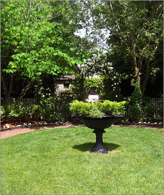 An urn at the center of the Benjamin Thompson House lawn features annuals, and behind that, a fenced patio where the residents can entertain and relax.