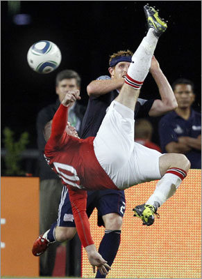 Manchester United forward Wayne Rooney (10) attempted a bicycle kick on goal, but failed to score against the defense of New England Revolution midfielder Pat Phelan during the first half.