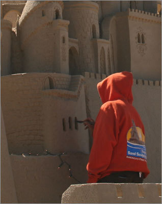 ...while another carved windows into the giant sand castle.