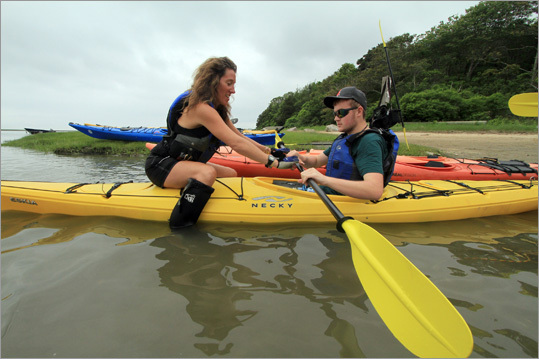 Kayak guide Erin Bates, left, helps Forrest McBarry, 17, of Greenfield hold his paddle correctly on Hemenway Landing on Salt Pond Bay in Eastham. Read: Surface attention