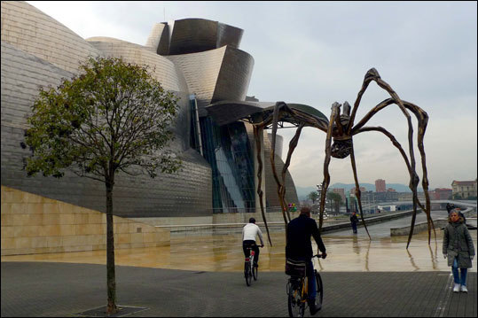 ''Maman,'' a sculpture by Louise Bourgeois, stands along the riverfront path adjacent to the Guggenheim Bilbao.