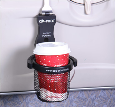 Hands-free cup carrier The Cup-Pilot lets you carry your coffee or other drink hands-free while you maneuver through the airport and board your plane. It also gives you a place to store your beverage during takeoff (when your tray table must be stowed), while using the restroom, and when riding in a train or vehicle. The simple and compact Cup-Pilot has a plastic ring with a mesh pocket for holding your drink, and an aluminum hook that fastens to your suitcase, airline seat pocket, or car's vent. It folds down nicely and stores in the included nylon stuff sack. Available for $19.95 through Cup-Pilot (877-287-1130, www.cup-pilot.com ). KARI BODNARCHUK