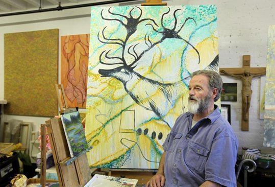 John Frederick Arens is a cutting-edge artist whose new series of paintings is inspired by ancient cave art. However, many are surprised to learn that the Needham-based artist is also a Catholic priest who teaches religion at St. Sebastian's School in Needham. Arens sits with one of his paintings in his Allston studio.