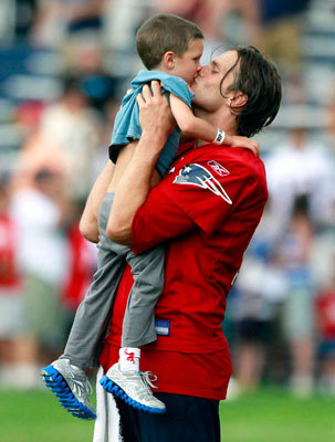 Aug. 9 Quarterback Tom Brady kisses his son Jack after practice at Patriots training camp in Foxborough.