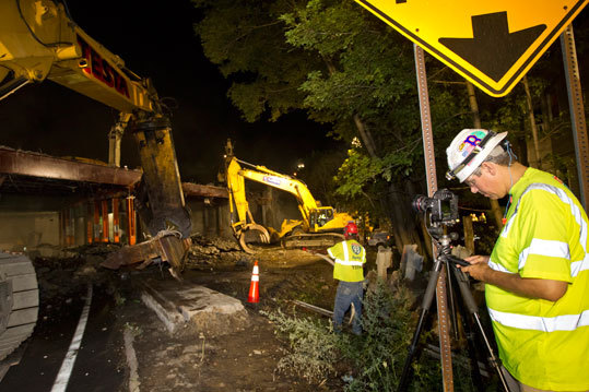 SetteDucatti (left) sets up a remote camera location, capable of taking a picture every 15 seconds, as the demolition crew tears down the Valley Street Bridge section of I-93 southbound on Friday, July 22, 2011.