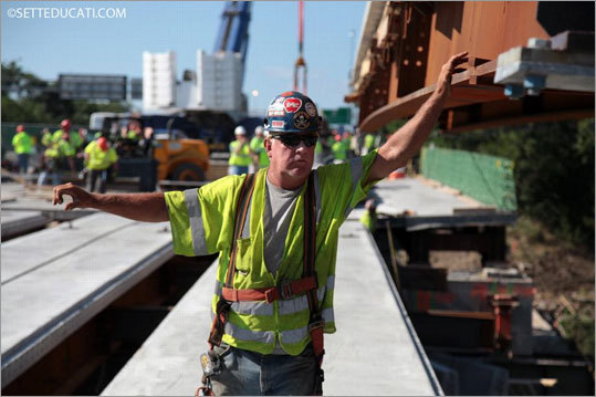 At left, Edward Finn Sr., a Local 7 ironworker and lead foreman for Saugus Construction, 'talks' to the crane operator using hand signals to guide a 78-foot-long, 100,000-pound section of breakdown lane into position for the Mystic River crossing on I-93 northbound. Wearing a full body harness to protect him, Finn is tethered to the deck panel. Once the section is set in place, carpenters descend on the bridge to set up forms for the concrete that will be poured the next day.