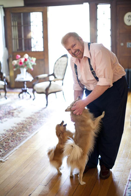 """'Even though I'm pushing 70, I can still build,'' said Davis, who lives here with his three Pomeranians. 'I thought, why don't I buy that house? This one's done. I love the house. It's beautiful, and I'll probably cry when I sell it. But I should, and move on. Onto something else."""" Davis plays with two of his dogs."""