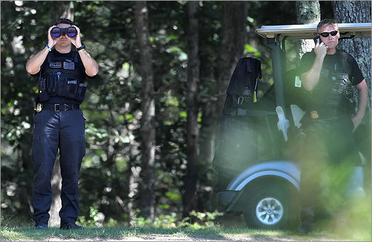 Security personnel for the president kept an eye on photographers while he golfed.