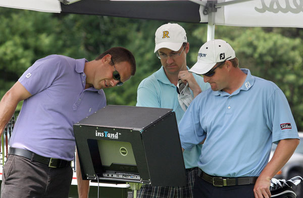 Reporter Michael Whitmer (center) takes it all in as Titelist club fitters James Kroeger (left) and Alex Stimpson analyze data from Whitmer's swings at a recent fitting in Acushnet.