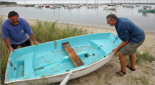 Frank DeSimone, left, of Oak Bluffs, and Peter Stam, of Vineyard Haven, moved a small boat inland at Vineyard Haven.