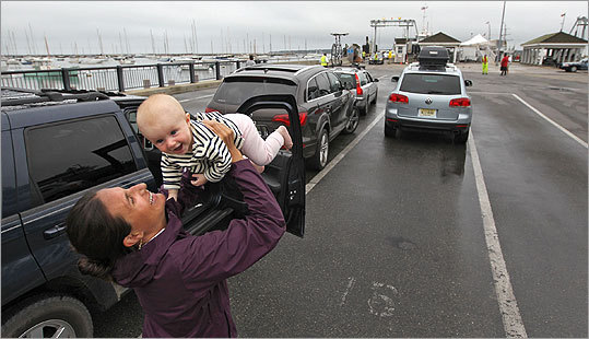 Jessa McIntosh, 33, entertained her 5-month-old daughter, Sayer McIntosh, both of New York City, as they wait with family in the short-term standby line to take the ferry with their vehicle at Vineyard Haven. McIntosh waited more than four hours to get onto a ferry after deciding to cut their vacation a day short to get off the island before Hurricane Irene hit.