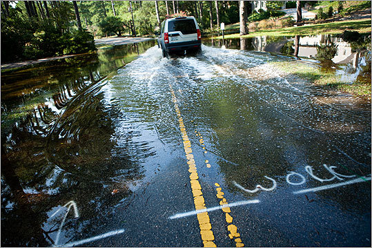 A driver passed through a street flooded by rain from the storm in Virginia Beach, Va.