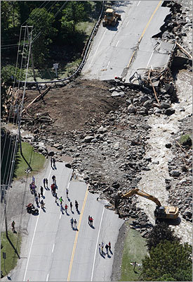 Irene also caused major damage in Vermont, where emergency management officials said they'd have to use helicopters to airlift food, water and supplies to flood-stricken towns that were cut off by road and bridge washouts. In this aerial photo people gathered alongside workers making repairs on Route 100 in Killington, Vt.