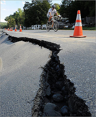 A bicyclist rode past a crack in the road along Route 9 in the aftermath of Irene, in Brattleboro, Vt.