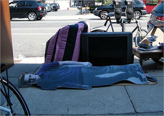 "A slightly-graffitied cardboard cutout of actor Robert Pattinson, who plays Edward Cullen in the ""Twilight"" movie series, rests on a Harvard Avenue sidewalk in Allston."