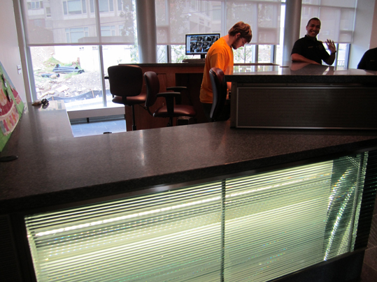 Security desks in an expansive lobby greet students as they walk in. The backlit desk is staffed at all time with guards who check students' swiped IDs to make sure they live in the building.