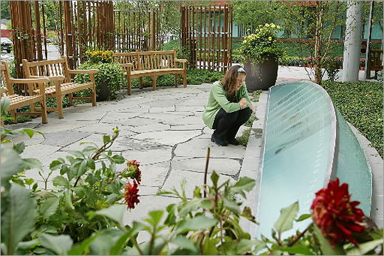 The TJX Cos. in Framingham has a Memorial Garden, designed in cooperation with the families of the seven TJX associates who were killed on Sept. 11, 2001. At left, a TJX employee visits the garden.