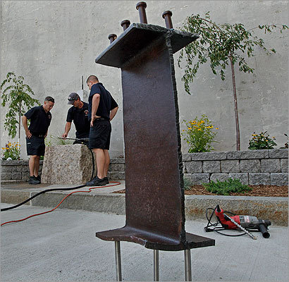 In August, outside the Salem Fire Headquarters on Layfayette Street, firefighters worked on a memorial to the 9/11 victims. They drilled holes in the top of a granite block where a piece of steel (foreground) from the World Trade Center site will be mounted. The 3-1/2 -foot piece of steel is the centerpiece of the memorial, honoring the nearly 3,000 people who died 10 years ago in New York, Pennsylvania and Washington, D.C. Left to right are Tom Brophy, Lieutenant Scott Hebert, and Manny Ataide.