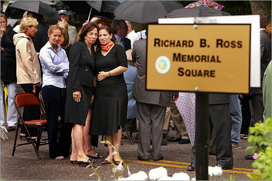 Judi Ross (center) and her daughter, Abigail, pause to reflect after a July 2004 ceremony dedicating a square in Newton's Oak Hill Village section in memory of Judi's husband and Abigail's father. Richard B. Ross was aboard American Airlines Flight 11 on Sept. 11, 2001.