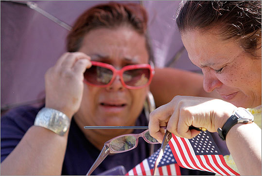 Sisters Ana, left, and Gloria Rodriguez, of Denver, mourn together during the Colorado Remembers 9/11 event in Civic Center Park Sunday. The sisters, originally of New York, lost a niece and a friend in the collapse of the World Trade Center.