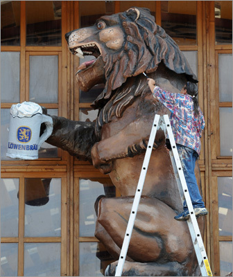 A man worked on a lion sculpture, the logo of the Bavarian Loewenbraeu brewery.