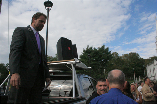 Senior Paster Jeramie Rinne stands on a flatbed truck moments before giving a quick sermon, reading a prayer that the audience echoed to celebrate the organization's accomplishment.