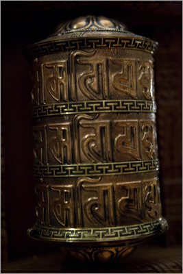 In Tibet, Buddhists travel to the Jowo Rinpoche to seek blessings for their studies or their business. When relatives are sick or dying, Tibetans offer gold to the statue, which represents Buddha at the age of 12. A Tibetan prayer wheel at the center.