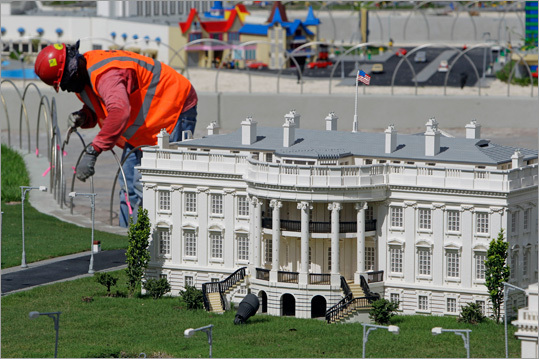 A worker painted a fence near a Lego model of the White House.