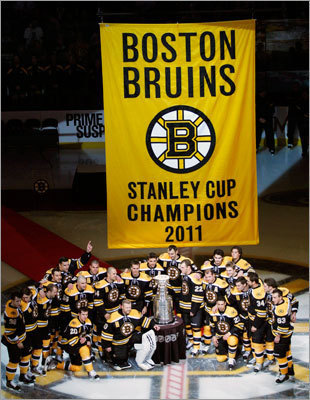 Bruins players posed with both the Cup and the 2011 championship banner before the the season opener against the Flyers on Oct. 6.