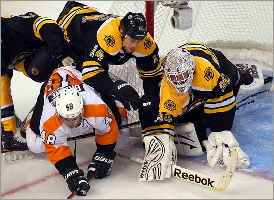 After a summer filled with merriment and celebrations, the Bruins finally got back to playing. The Flyers' Danny Briere, and Bruins Joe Corvo and Tim Thomas tangled as a loose puck crossed in front of the net in the third period.