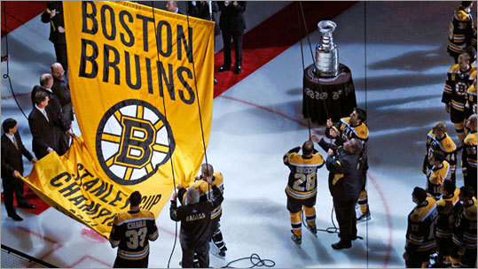 Bruins goalie Tim Thomas (bottom) had his hands on one of the ropes as the banner was raised.