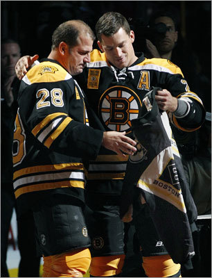 Retired Bruin Mark Recchi (left) returned for the banner-raising ceremony and dressed in full uniform. He was given the coveted 'team jacket,' which the Bruins passed from player to player during the playoffs to recognize important individual efforts during their title run.