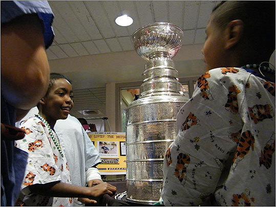 In the hallway of a fourth-floor pediatrics wing of Boston Medical Center, 10-year-old Shykein Basden (left) and his friend 8-year-old Gaines (right) were among the first at the medical center to lay hands on the Stanley Cup.