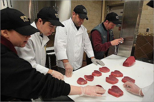 Seafood staff studied the yellowfin tuna portion sizes and cuts.
