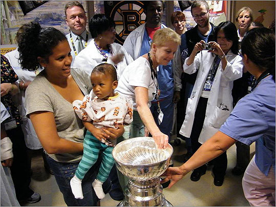 Patients, families and staff, including registered nurse Mary Ellen McDonough (center, touching Cup) were thrilled to see the coveted Cup in person.