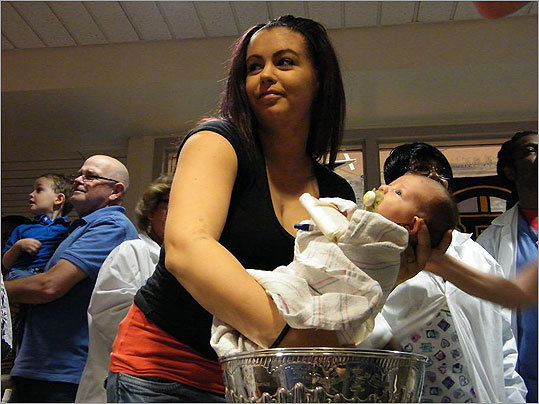 A woman holds an infant above the Cup's bowl.