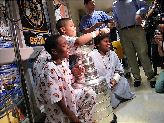 With less than two weeks left before the Boston Bruins will have to return the Stanley Cup back to its trustees, patients and staff at Boston Medical Center had a chance this afternoon to spend several precious moments with the iconic hockey hardware won by last season's champions. Three young patients, including Gaines (center, holding out a championship ring) pose for photos with the Stanley Cup at Boston Medical Center Tuesday afternoon.