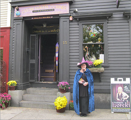 Locals and visitors dress up in costumes for Halloween all month long. Laura Sekinger hands out flyers in front of Crow Haven Corner witch shop.