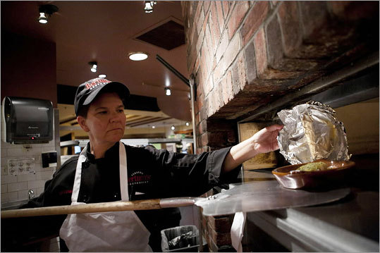 Each prepared dish, carefully labeled, was wrapped in aluminum foil and placed in the 575-degree brick oven.
