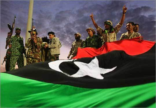 Soldiers who fought to oust Moammar Khadafy waved to a crowd in Benghazi yesterday. Transitional leaders say a new interim government is to be formed within a month.