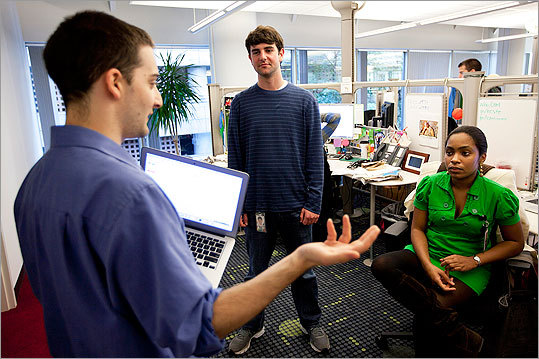 Dan Rubin-Wills, an account strategist, left, meets with Ezra Brettler, center, and Sylvie Armand, who started in September as account coordinators.