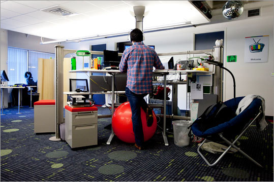 Brian Gargan, an account executive for TV ads, works at his desk. Balance balls are often used for chairs.